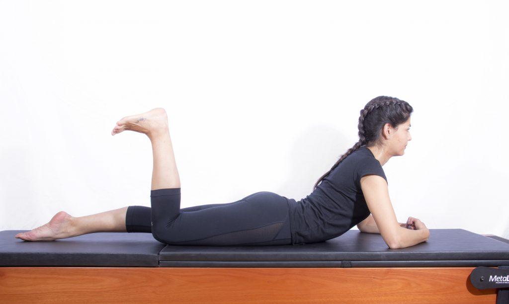 mulher realizando exercício de pilates chamado the one (single) leg kick